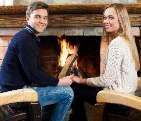 暖炉の前に座る男女
